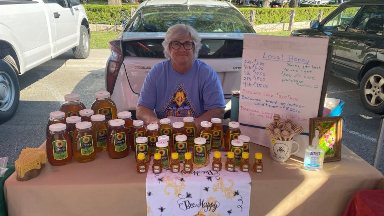 An older woman sits inside her vendor tent at the San Marcos Farmers Market in front of a line of parked cars. She sits behind a table of various sizes of bottles of honey, a display of yellow business cards and to the woman's left is a white sign with handwritten text reading prices of various amounts of honey, soap, wood or leather conditioner and beeswax candles and giftboxes.