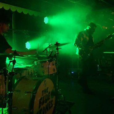 Drummer, Justin Tessier(left), and Singer/Guitarist, Tarek Jafar(right) playing on stage with a green backlight