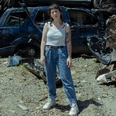Picture of the lead singer used for the album cover. She is standing in front of a junkyard with crushed cars and debris.