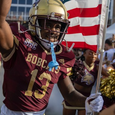 Texas State football player in Maroon jersey and gold helmet running onto the football field with an American flag with his team and cheerleaders running alongside him
