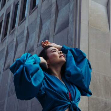 Mitski, a woman, wearing a royal blue long sleeve shirt or dress, with her hands up on her head and face, looking towards the sky with a grey building with windows in the background,