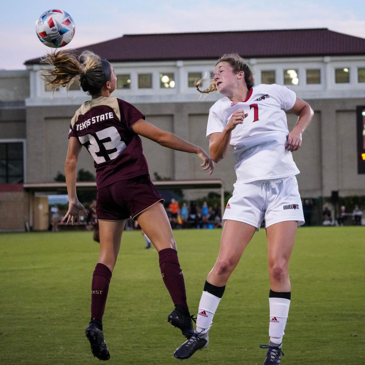 Bobcat player goes up to compete for a header against Arkansas St. Player. (Gabie Jones)
