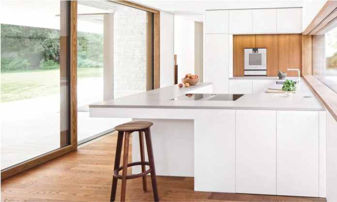 """The model """"Kitchen full of light"""" speaks for itself: with soft matt lacquer fronts, daylight is reflected here and floods the room with brightness.  A worktop made of quartz composite concrete and a wood-clad back wall serve as a gentle boundary.  (Photo: selektionD)"""