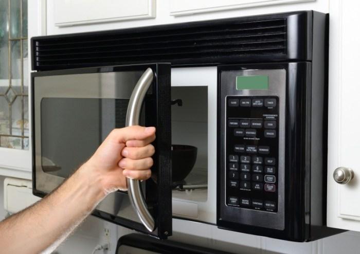 Рука открывает микроволновую печь