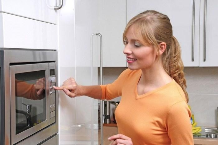 Девушка включает микроволновую печь