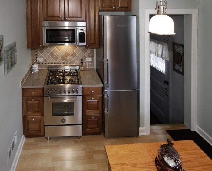 Серебристый холодильник на маленькой кухне в нише у стены