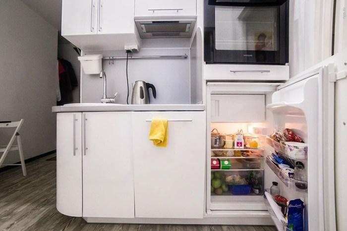 Маленький холодильник спрятан за фасад шкафа