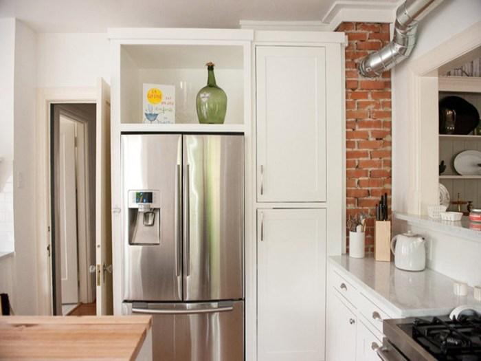 Холодильник у двери встроен в систему шкафов