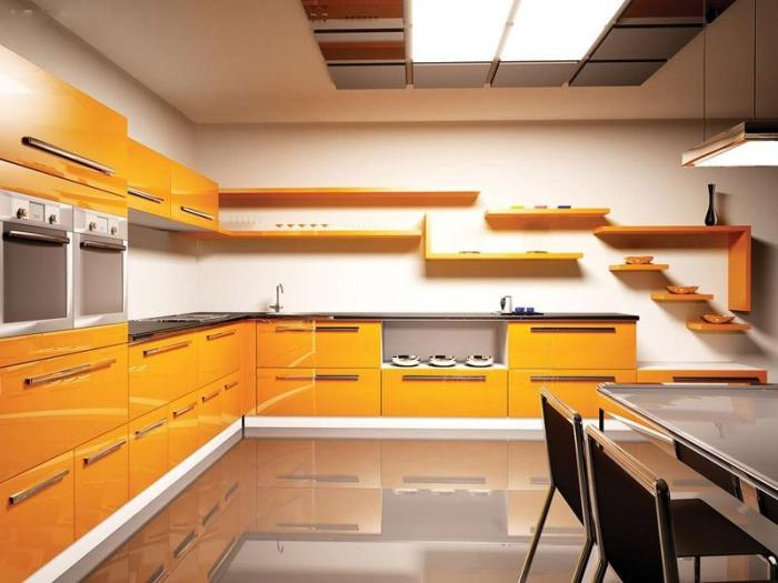 Оранжевая мебель кухни на фоне стен сливочно-белого цвета