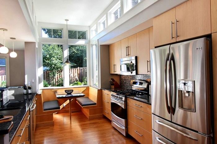 Кухня-пенал со столом и диванчиками в дальней торцевой части у окна