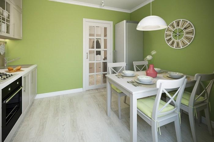 Белый стол и стулья простой формы на зеленой кухне