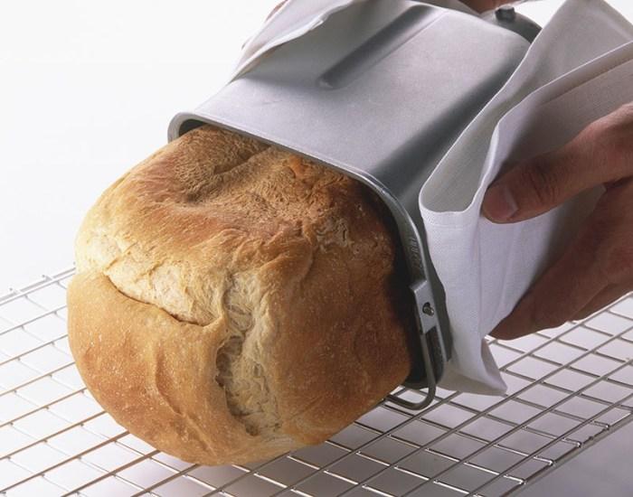 Готовая горячая буханка вынимается из чаши хлебопечки