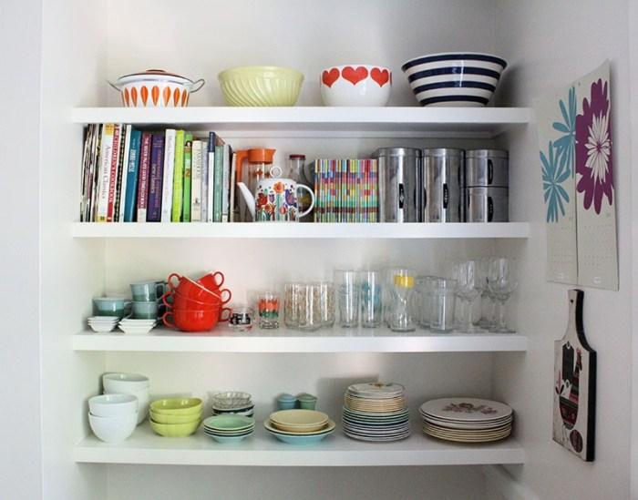 Открытые полки в нише с разной посудой и книгами