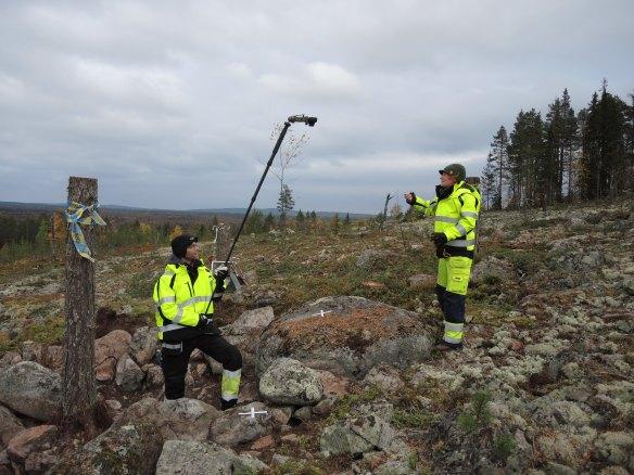 Arkeologerna Lars Backman och Frida Palmbo arbetar med lodfotografering av en boplatsgrop i klapper på Öberget © Norrbottens museum