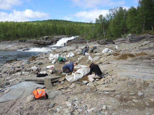 Foto på arkeologer i arbete, fors i bakgrunden.