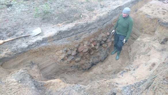 En arkeolog står i ett 1,5 meter djupt undersökningsschakt, invid en stor kokgrop