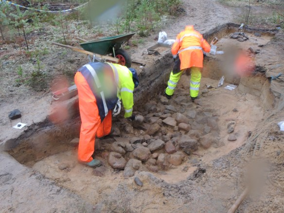Foto med två arkeologer som undersöker en stor kokgrop