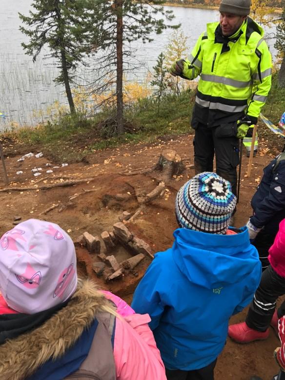 Foto på arkeologisk undersökning, med skolbarn som lyssnar på en arkeolog