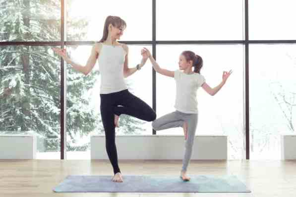 adulta and child are doing tree pose on a grew mat in front of a window, they are holding hands and looking at each other