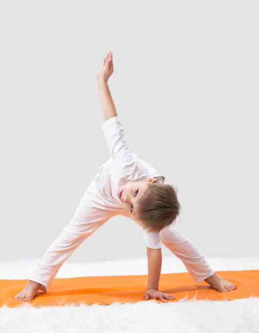 little boy doing wide legged forward fold twist yoga pose with one hand on an orange yoga mat and the other arm reaching up to the sky