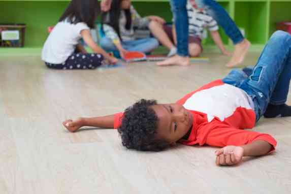child laying down not participating in yoga class for kids