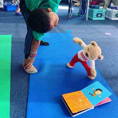 Meddy teddy is doing triangle yoga pose with a child on their yoga mat