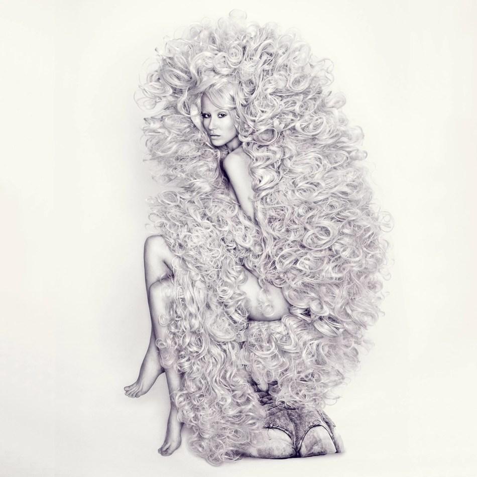 Fotografie von Frank und Steff. In der Ausstellung Fumes and Perfumes 6.0 im Züblin Parkhaus in Stuttgart. Zu sehen ist eine unbekleidete Frau, die auf einem Hocker aus einem Elefantenbein sitzt. Sie blickt den Betrachter direkt an. In schwarz-weiß. Ihre Haare bedecken fast den gesamten Körper. Ihre Beine sind überschlagen.