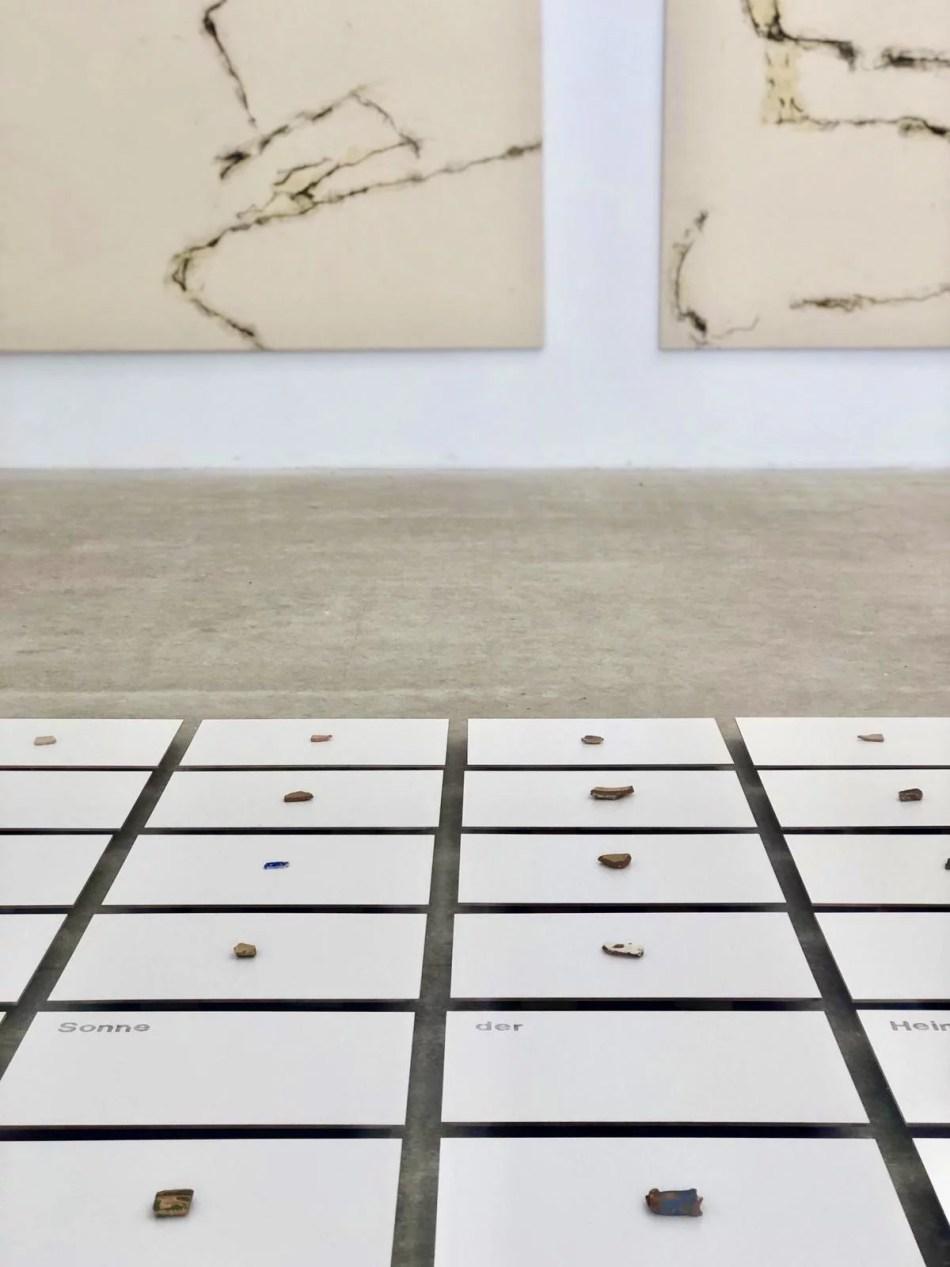 Detail der Installation von Ralf Bertscheit, 56 Hartfaserplatten mit Wort- und Fundstücken
