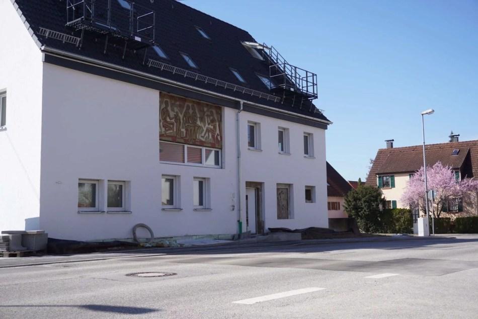 Das Foto zeigt das renovierte Ateliergebäude Pfeiffers (heute Wohnhaus). Es liegt direkt an der Straße, hat ein dunkles Dach und ist weiß angestrichen. An der Fassade ist Pfeiffers Kunst zu erkennen.