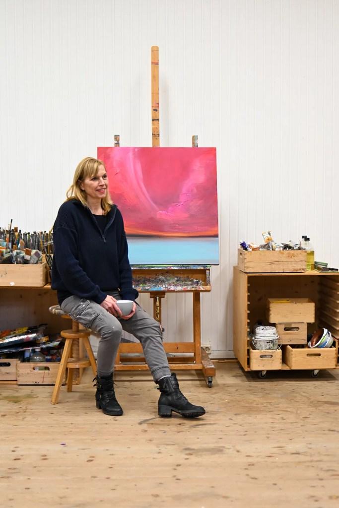 Die Künstlerin Sigrid Nienstedt sitzt mit einer Tasse in der Hand vor ihrer Staffelei.