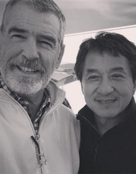 Pierce Brosnan enjoys a moment between scenes with Jackie Chan