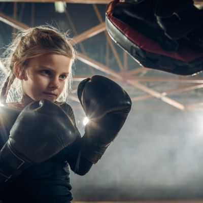 Small girl exercising boxing with unrecognizable coach in a health club.