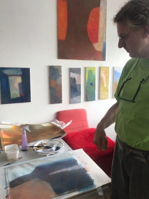 Jan Baas tijdens ons atelierbezoek bij een aquarel. De olieverfschilderijen hangen op de achtergrond. Nog niet helemáal klaar.