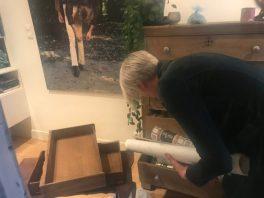 Anneke Siesling zoekt het meest passende behang voor op het kastje.