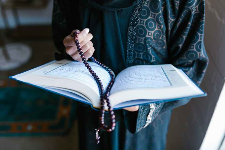 crop photo of woman holding a prayer beads and holy book