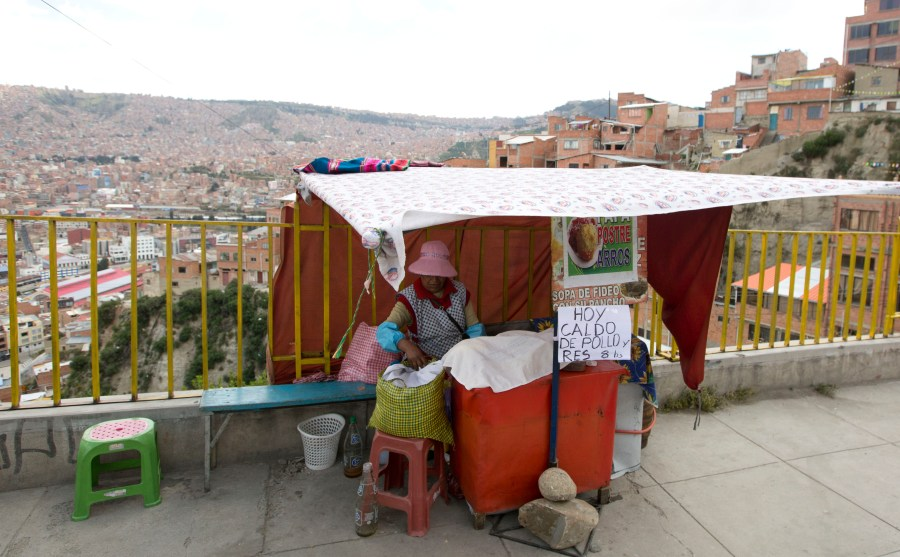 A street vendor waits for customers at her stall, where she has a sign that reads in Spanish