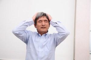 頭を抱える悩む中高年男性