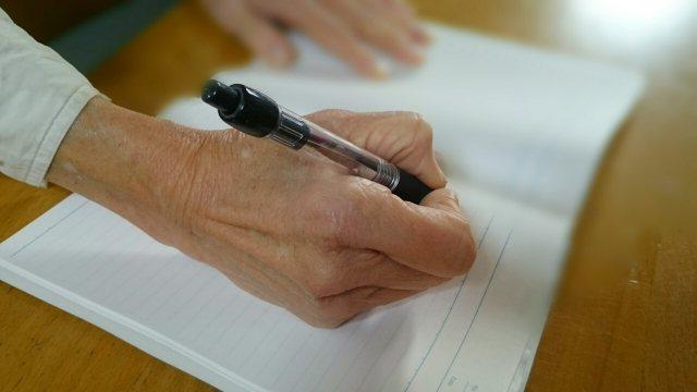 手紙を書く老人の手