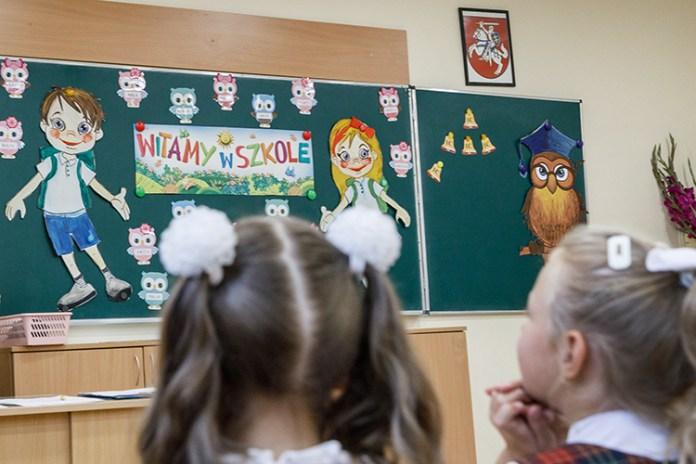 Dzieci w szkole na Litwie patrzą na tablicę w czasie kwarantanny wprowadzonej przez pandemię koronawirusa.
