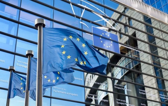 Flagi Unii Europejskiej przed budynkiem Parlamentu Europejskiego