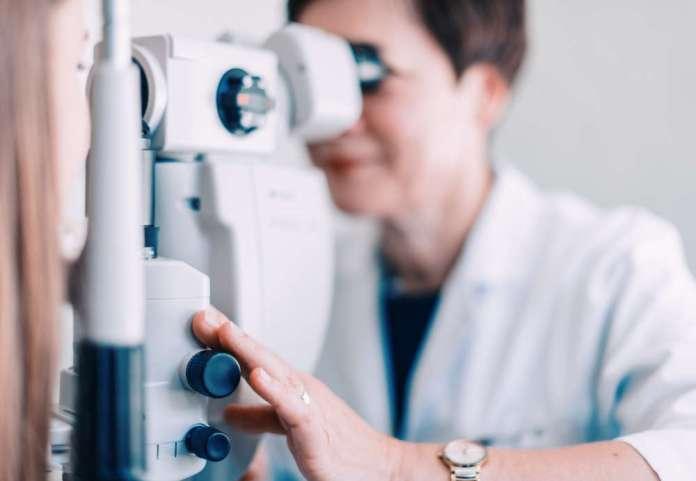 Kobieta patrzy w mikroskop i uśmiecha się ze świadomości, że jest robione jej zdjęcie. Na ręku zegarek.