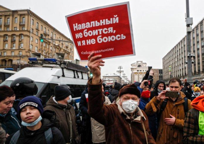 """Człowiek z plakatem """"Nawalny nie boi się, i ja się nie boję"""" stoi na ulicy."""