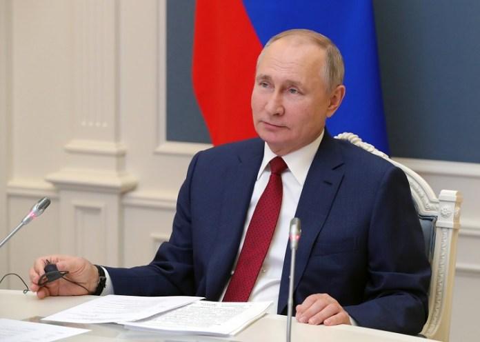 Prezydent Rosji, Władimir Putin, siedzi przy biurku i patrzy w dal z pobłażliwym uśmiechem