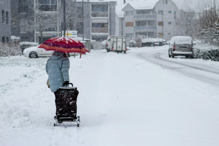 Osoba w szarym płaszczu trzyma czerwony parasol idąc po pokrytej śniegiem ulicy