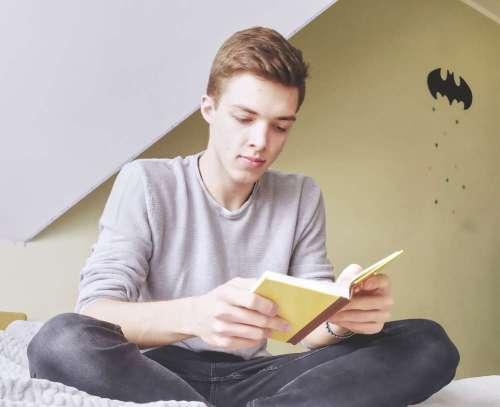 Rafał Szipkowski siedzi i czyta.