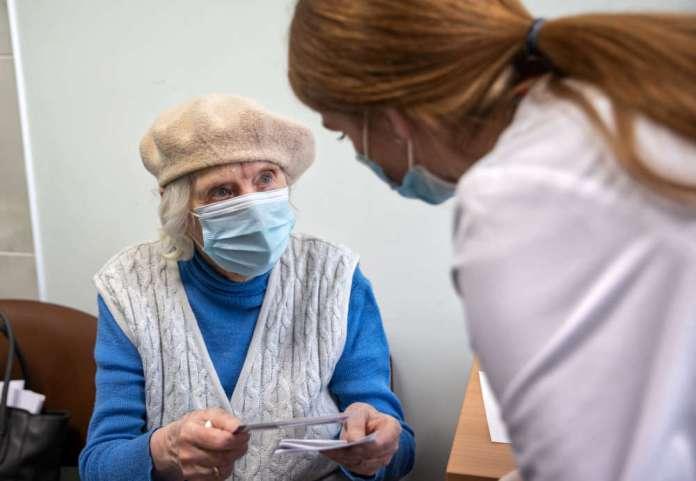 Seniorka siedzi i patrzy na medyka.