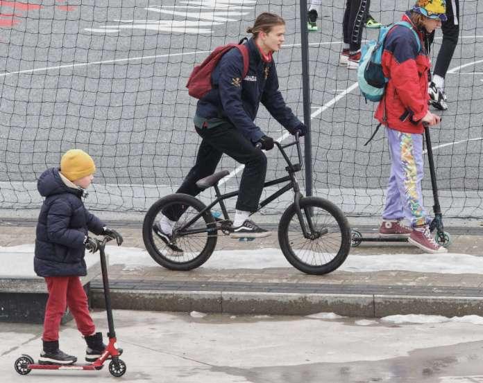 Młodzież jedzie na hulajnogach i rowerach zimą w Wilnie