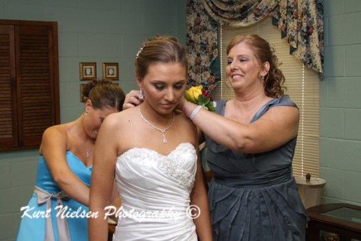 mom putting on bride's necklace