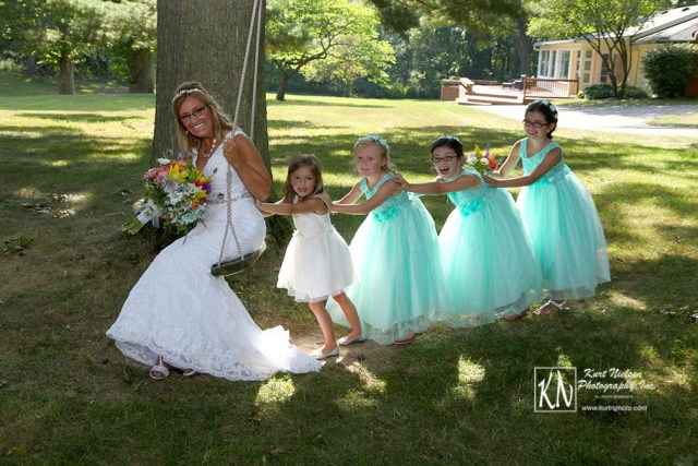 bride being pushed on a tree swing by the flower girls