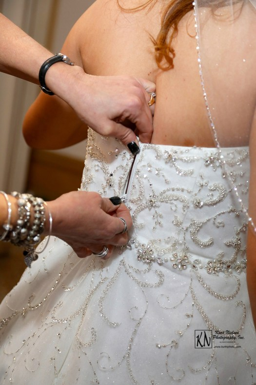zipping the bride's dress